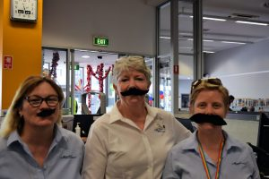 Library staff with fake moustaches